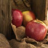 在土气厨房设置的红色苹果与老木箱和hes 免版税库存照片