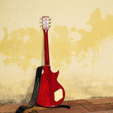 在土气墙壁倾斜的电吉他 免版税库存照片