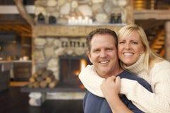 在土气壁炉的富感情的夫妇在原木小屋 免版税库存图片