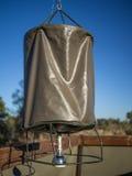 从在土气徒步旅行队的一条绳索分与的简单的金属和帆布桶阵雨野营,博茨瓦纳,非洲 免版税库存照片