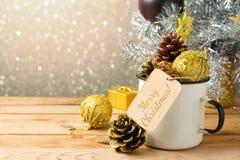 在土气搪瓷杯子的圣诞节装饰在木桌上 免版税库存图片