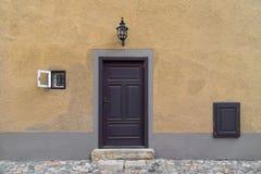 在土气旧世界样式水泥黄色墙壁w上的老木门 库存图片