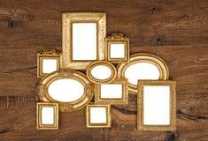 在土气木墙壁的古色古香的金黄框架 库存图片