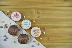 在土气木头的愉快的复活节自创巧克力和香草杯形蛋糕 免版税库存照片