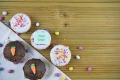 在土气木头的愉快的复活节自创巧克力和香草杯形蛋糕 库存图片