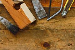 在土气木工作台的老diy工具 免版税库存图片