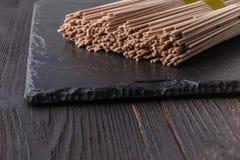 在土气木板的干荞麦soba面条 图库摄影