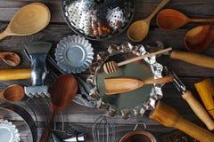 在土气木桌上的各种各样的厨房器物 库存照片