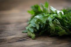 在土气木桌上的新鲜的绿色莳萝和荷兰芹草本 与拷贝空间的顶视图 库存照片