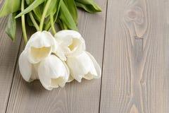 在土气木桌上的白色郁金香 图库摄影