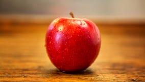 在土气木桌上的红色湿苹果 图库摄影