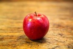 在土气木桌上的红色湿苹果 免版税图库摄影