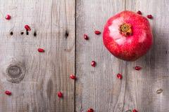 在土气木没有漆的桌上的整个红色成熟水多的石榴 图库摄影