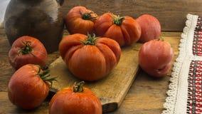 在土气木砧板和木桌的蕃茄 库存照片