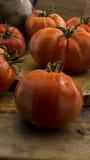 在土气木砧板和木桌的蕃茄 免版税库存图片