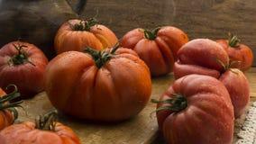 在土气木砧板和木桌的蕃茄 免版税库存照片