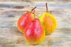 在土气木背景的三个成熟黄色和红色梨 库存图片