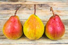 在土气木背景的三个成熟黄色和红色梨 免版税库存图片