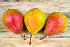 在土气木背景的三个成熟黄色和红色梨 图库摄影