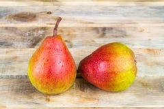 在土气木背景的两个成熟黄色和红色梨 图库摄影