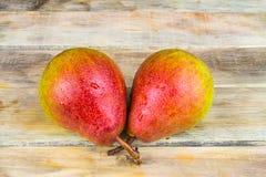 在土气木背景的两个成熟黄色和红色梨 库存图片