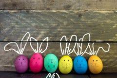 在土气木背景的复活节彩蛋逗人喜爱的兔宝宝 免版税库存图片