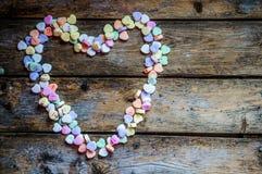 在土气木背景的心脏糖果 库存图片