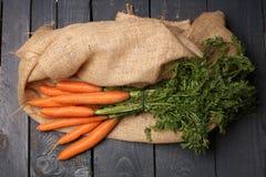 在土气木背景的新红萝卜束 免版税库存照片