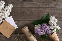 在土气木背景的淡紫色开花与招呼的消息的空的空间 剪刀,螺纹卷轴,小信封 库存图片