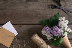 在土气木背景的淡紫色开花与招呼的消息的空的空间 剪刀,螺纹卷轴,小信封 免版税库存照片