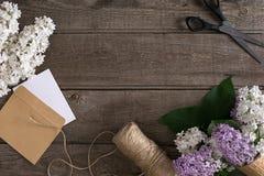 在土气木背景的淡紫色开花与招呼的消息的空的空间 剪刀,螺纹卷轴,小信封 免版税库存图片