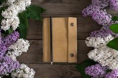 在土气木背景的淡紫色开花与招呼的消息的笔记本 顶视图 免版税库存照片