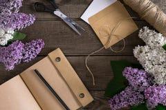 在土气木背景的淡紫色开花与招呼的消息的笔记本 顶视图 库存照片