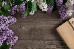 在土气木背景的淡紫色开花与招呼的消息的笔记本 顶视图 免版税图库摄影