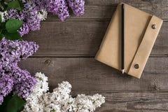 在土气木背景的淡紫色开花与招呼的消息的笔记本 顶视图 免版税库存图片