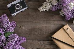 在土气木背景的淡紫色开花与招呼的消息的笔记本 顶视图 库存图片