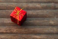 在土气木背景的礼物盒 在红色包装纸的生日礼物 库存照片