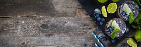 在土气木背景的蓝莓mojito 免版税库存照片