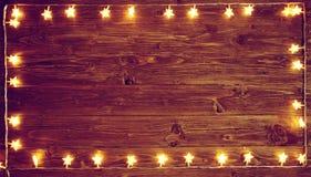 在土气木背景的黄色圣诞灯 圣诞节或新年概念 被定调子的图象 免版税库存照片