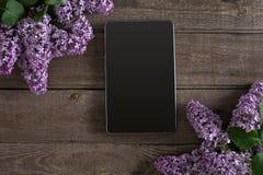 在土气木背景,有空的空间的片剂的淡紫色开花招呼的消息的 顶视图 库存照片