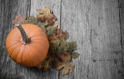 在土气木头的南瓜和秋天叶子 免版税库存图片