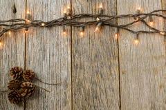 在土气木头的圣诞灯和杉木锥体 图库摄影