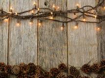 在土气木头的圣诞灯和杉木锥体 库存照片