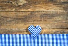 在土气木头的慕尼黑啤酒节心脏蓝色和白色方格的样式 库存图片