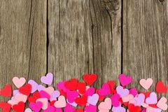 在土气木头的纸情人节心脏底部边界 库存图片