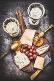 在土气板材的开胃美好的乳酪选择用酒、葡萄和蜂蜜芥末酱 免版税库存图片