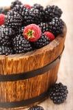 在土气样式的成熟水多的莓果黑莓和莓 免版税库存照片