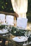 在土气样式的装饰的典雅的木婚礼桌与玉树和花、瓷板材、玻璃和椅子 免版税库存照片