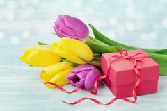在土气桌上的礼物盒和郁金香花为3月8日,国际妇女天,生日或母亲节 免版税库存图片
