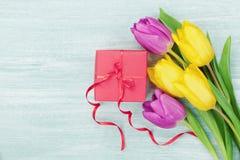 在土气桌上的礼物盒和郁金香花为3月8日,国际妇女天,生日或母亲节 库存照片